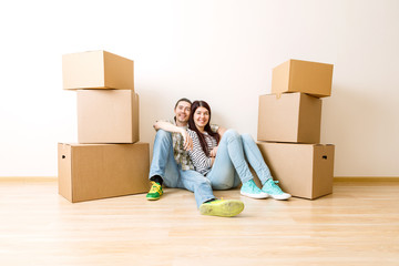 Photo of young couple sitting on floor among cardboard boxes