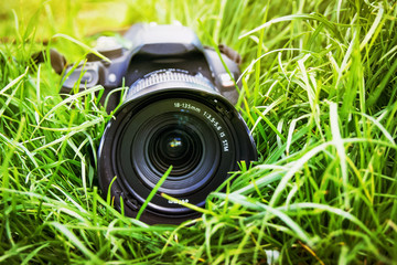 Advertising of professional photographic equipment. Camera lies in grass_
