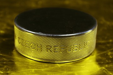 Hockey puck with the inscription `Czech Republic` on the golden background.Black puck  on golden background. We are Czech fans and we want gold medal.
