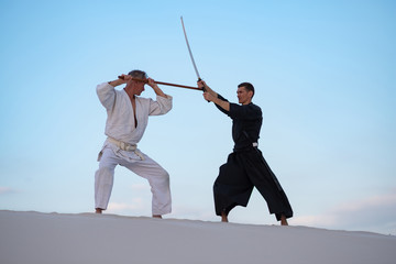 Two focused man, in Japanese clothes,are practicing martial arts