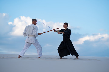 Two resolute men, in Japanese clothes, are practicing martial arts