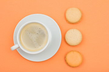 Cup of coffee and delicious macarons cakes on peach background