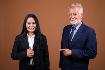 Mature multi-ethnic business couple against brown background