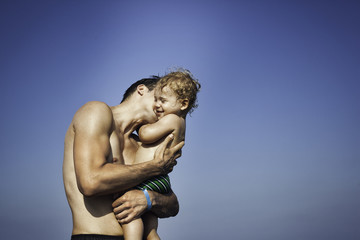 Father kissing his son on the beach against blue sky