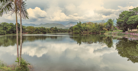 panoramic of amazing and bucolic lake with reflections in the water and palms in thailand