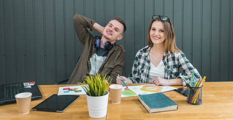 Two colleagues apprentices near working place in modern green office