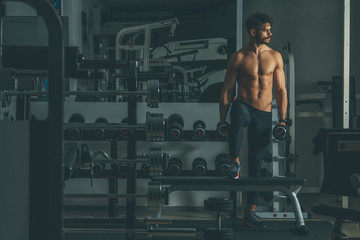 Strong and handsome young man doing exercise with dumbbells