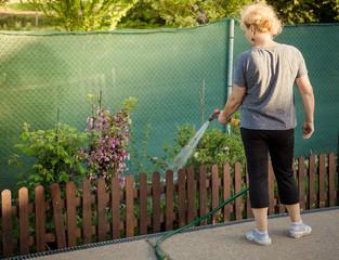 Woman watering garden with hose gun
