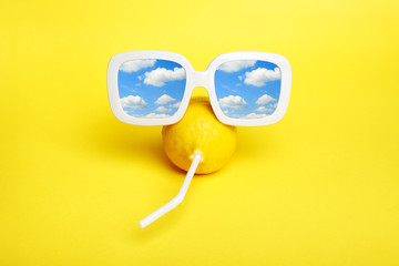 Minimal Mod lemon in sunglasses with straw on summer vacation.