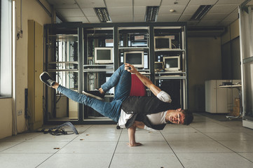 Stylish bboy performing a break dance stance in a computer room in abandoned building