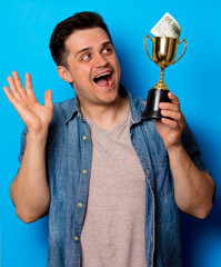 Young man in jeans shirt with golden cup and money on blue background
