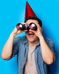 Young man in birthday hat with binoculars on blue background