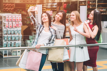 Dark-haired girl in pants is taking picture of herself with company. They are in mall. Girls are posing and having some fun.