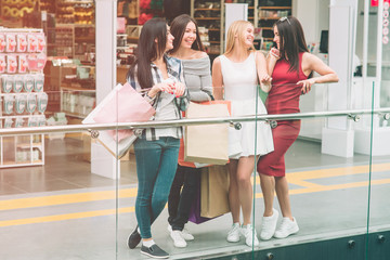 Attractive and awesome girls are standing at the edge of floor and looking at each other. They are laughing. Girl in red dress is holding phone.