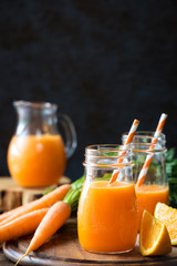 Healthy detox orange carrot smoothie or juice in glass jars on wooden background with fresh ingredients. With pleanty of copy space for your text
