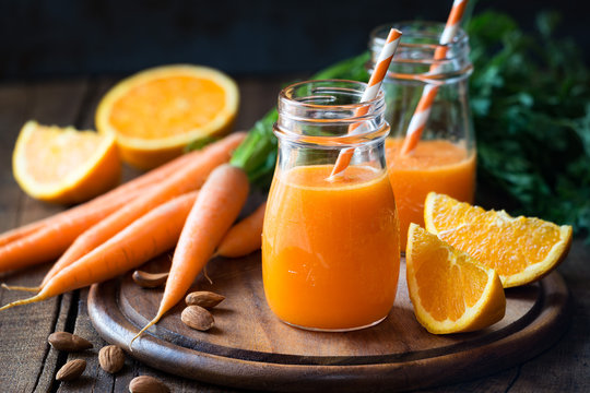 Healthy detox orange carrot smoothie or juice in glass jars on wooden background with fresh ingredients