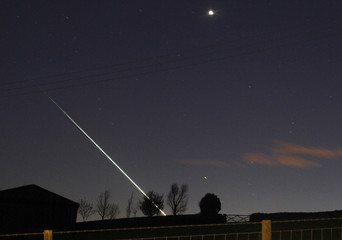 A meteorite creates a streak of light across the night sky over the North Yorkshire moors at Leaholm, near Whitby, northern England