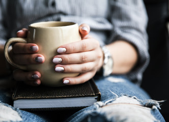 A young girl with a beautiful manicure holds a book with a cup of coffee. Fashion style