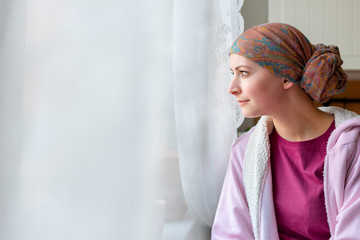 Young adult female cancer patient wearing headscarf and bathrobe sitting in the kitchen looking out window.