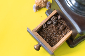 close up selective coffee beans and grinded coffee bean in vintage wooden coffee grinder on yellow background