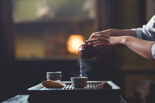 Female hands pouring tea from teapot