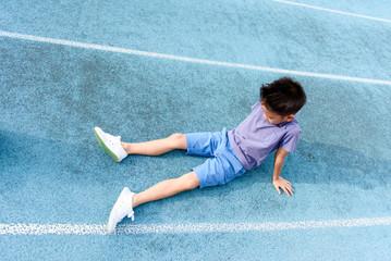 Boy rest on the blue track after sport