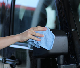 Autoscheibe mit Lappen und Hand reinigen