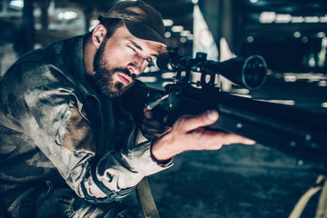 Portrait of brunette is taking aim. He is looking through lens. Guy is holding rifle with right hand and keeping his left one on trigger. Man is ready to shoot.