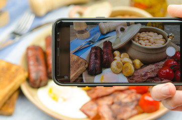 Man taking photo of traditional full English breakfast on smartphone. Taking food photo with mobile phone