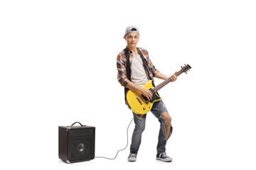 Teenage boy with an electric guitar and an amplifier
