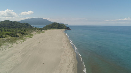 Aerial view of coastline with sandy beautiful beach. Philippines, Luzon. Ocean coastline with turquoise water. Philippines, Luzon. Tropical landscape in Asia.