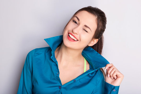 Close up confident young woman holding shirt collar and smiling