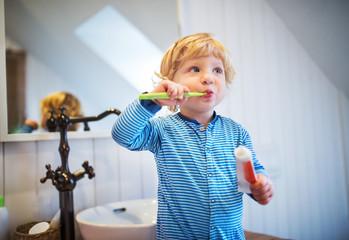 Cute toddler boy brushing his teeth in the bathroom.