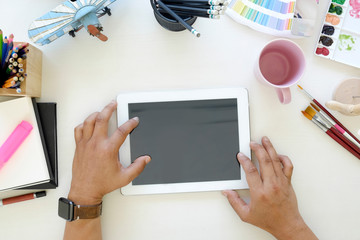 Designer working with tablet on desk in studio.