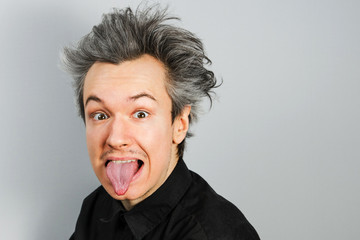 Young guy shows tongue like Albert Einstein on gray background.