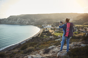 Back of girl in denim clothing taking picture of coastline from high. She is carrying backpack behind. Copy space in left side
