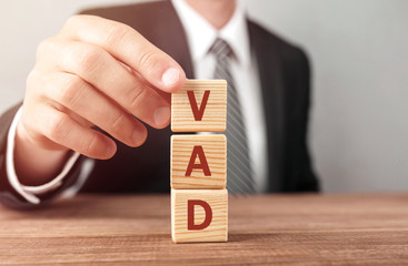 Businessman made word VAD with wood building blocks.