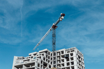 Building of modern residential buildings, construction crane, blue sky.