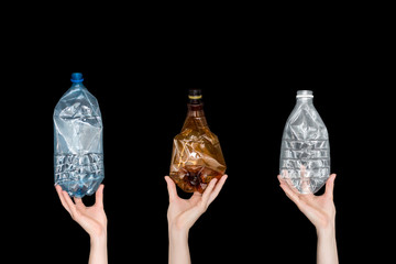 Female hands holding empty crushed plastic bottles isolated on black background. Recyclable waste. Recycling, reuse, garbage disposal, resources, environment and ecology concept.