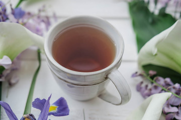 Herbal tea with wisteria, irises, white callas on gray background.