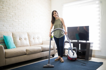 Young woman hoovering carpet with vacuum cleaner