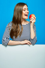 Smiling woman biting red apple. White banner with copy space