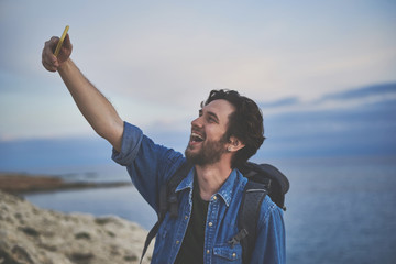 Excited young man is taking photo of himself on mobile phone. He is standing on cliff near the sea and laughing