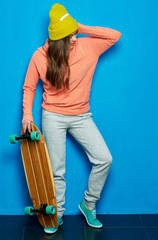 Girl holding skateboard and looking down.