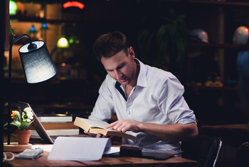 Businessman Caucasian men are working at night. With a laptop, books and documents is on the table.