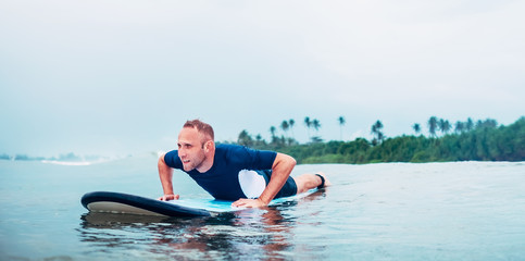 Surfer man floats on surfboard