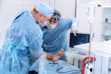 A team of doctors in sterile medical gowns perform surgery in a surgical room. The surgeon shows the diagnostic equipment and communicates with the assistant.