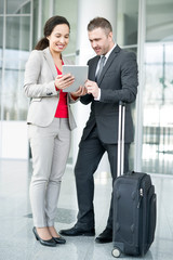 Full length portrait of successful business couple, man and woman, standing in hall of modern airport with suitcase and using digital tablet