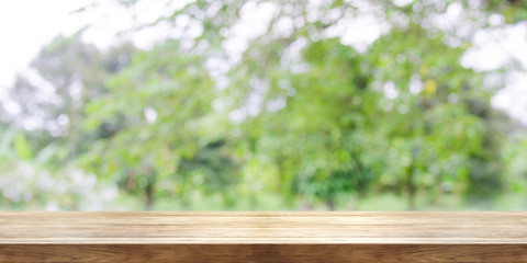 Empty wooden table top with blurred green garden background. Panoramic banner.