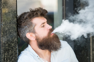 Side view attractive hipster man in urban context standing next to wall with marble siding. Good looking bearded man smoking electronic cigarette, habits and youth fashion